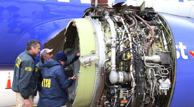 National Transportation Safety Board investigators examine damage to the engine (NTSB/AP)