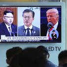 People watch a TV screen showing file footage of U.S. President Donald Trump, right, South Korean President Moon Jae-in and North Korean leader Kim Jong Un (Ahn Young-joon/AP)