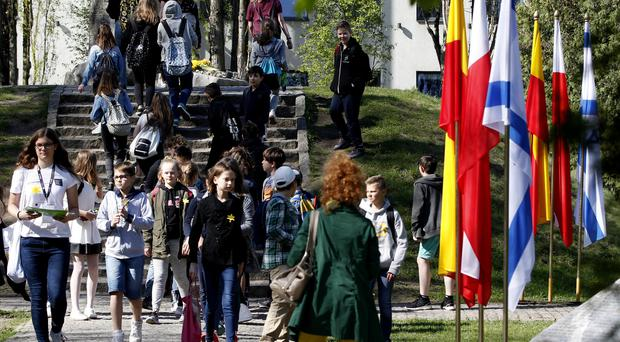 People with daffodils gather for non-official anniversary ceremonies (Czarek Sokolowski/AP)