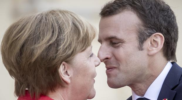 French President Emmanuel Macron, right, is welcomed by German Chancellor Angela Merkel (Michael Kappeler/AP)