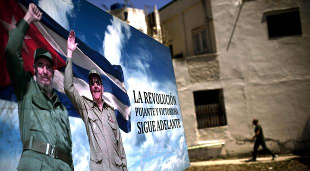 A poster of Fidel Castro and Cuba's President Raul Castro stands in Havana (Ramon Espinosa/AP)