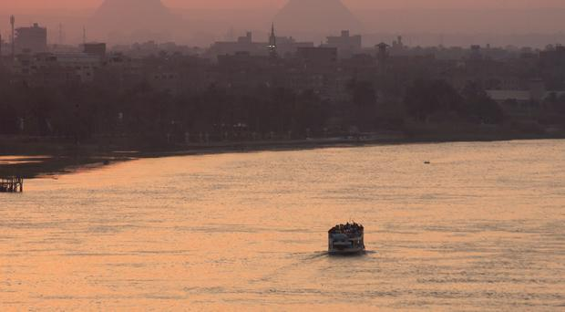 Holidaymakers take a boat tour on the Nile River past the Great Pyramids (Amr Nabil/AP)