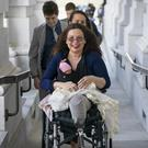Sen Tammy Duckworth arrives at the Capitol with her new daughter, Maile (J Scott Applewhite/AP)