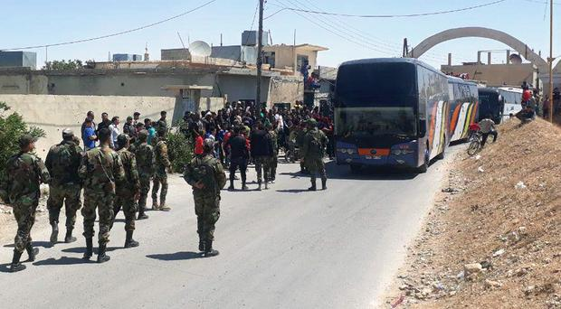 Syrian government forces oversee the evacuation by bus of rebels and their family from the towns of Ruhaiba (SANA/AP)