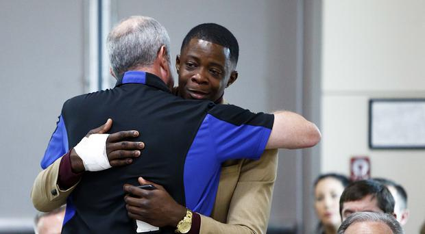 James Shaw, right, gets a hug from Waffle House chief executive Walt Ehmer (Wade Payne/AP)
