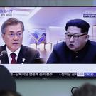 People watch a TV screen showing file footage of South Korean President Moon Jae-in and North Korean leader Kim Jong Un (Lee Jin-man/AP)