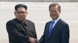 North Korean leader Kim Jong Un shakes hands with South Korean president Moon Jae-in as Mr Kim crossed the border into South Korea for their historic face-to-face talks (Korea Broadcasting System/AP)