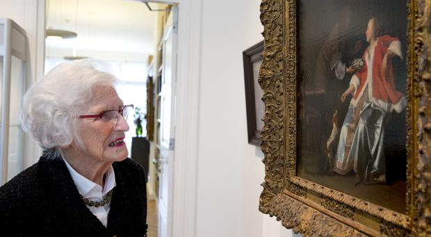 Charlotte Bischoff van Heemskerck looks at her painting The Oyster Meal by Jacob Ochtervelt (Peter Dejong/AP)