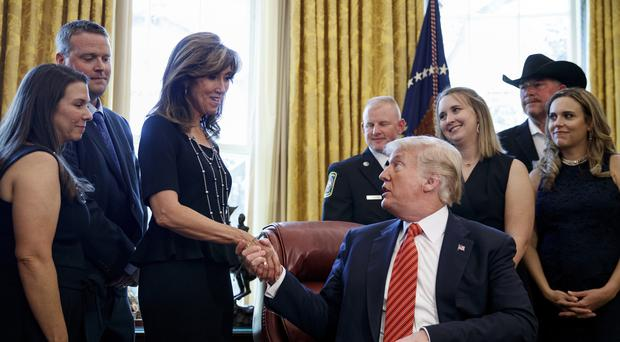 President Donald Trump shakes hands with pilot Tammie Jo Shults (Carolyn Kaster/AP)