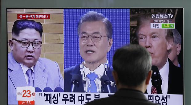 A man watches a TV screen showing footage of Donald Trump, Moon Jae-in and Kim Jong Un, (Lee Jin-man/AP)