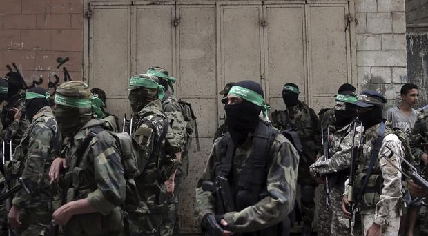 Masked Hamas gunmen attend a funeral for six fighters who were killed in an explosion in Deir el-Balah, central Gaza Strip (Khalil Hamra/AP)