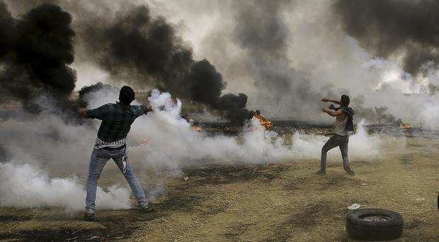 Palestinians throw back tear gas canisters at Israeli soldiers in a protest at the Gaza Strip's border with Israel (Adel Hana/PA)