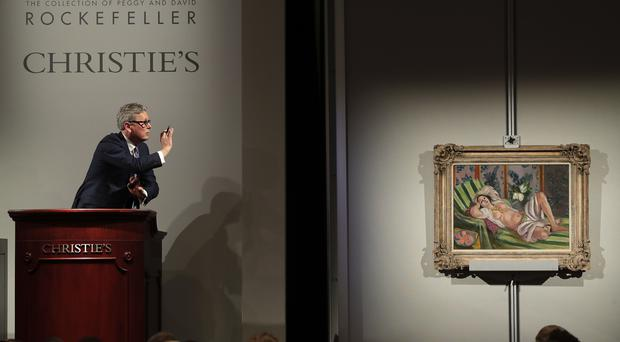 "Global president of Christie's Jussi Pylkkanen taps the gavel on the podium for the final sale of Henri Matisse's ""Odalisque couchee aux magnolias"" (Julie Jacobson/AP)"