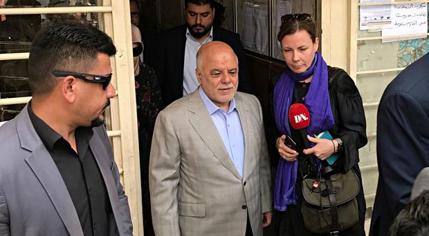 Iraq Prime Minister Haider al-Abadi, centre, leaves a polling station in Baghdad after casting his ballot in the country's parliamentary elections (AP)