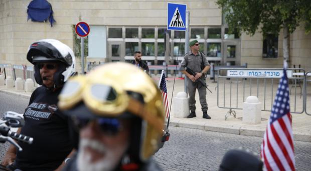 Security personnel stand guard as riders from a motorcycle club arrive at the new US embassy on a group ride from the old embassy (Ariel Schalit/AP)