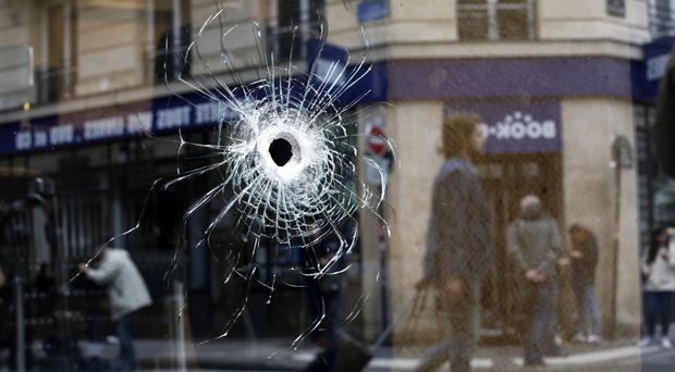 A bullet hole seen on the window of a cafe located near the area where the assailant of a knife attack was shot dead by police in Paris (Thibault Camus/AP)