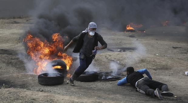 Palestinian protesters burn tyres during a protest on the Gaza Strip's border with Israel (AP)