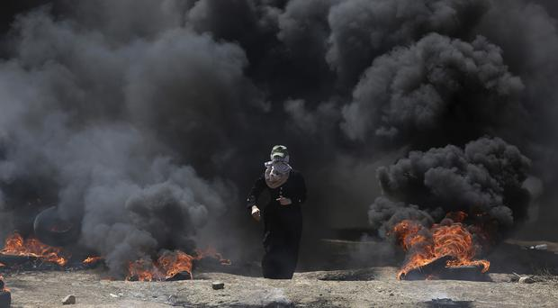 A Palestinian woman walks through black smoke from burning tires during a protest on the Gaza Strip's border with Israel (AP)
