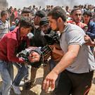 Palestinians carry an injured man during clashes with Israeli forces near the border between the Gaza strip and Israel east of Gaza City