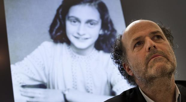 A picture of Anne Frank is projected as director Ronald Leopold of the Anne Frank Foundation listens during a press conference at the foundation's office in Amsterdam (Peter Dejong/AP)