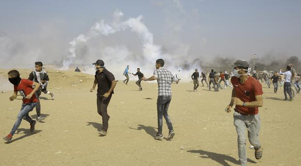Palestinian protesters run for cover from teargas fired by Israeli forces near the border fence, east of Khan Younis, in the Gaza Strip (AP)