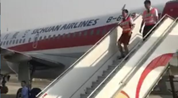 Crew members leave the Sichuan Airline flight