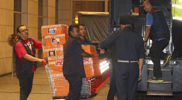 Police prepare to load confiscated items into a truck in Kuala Lumpur (AP)