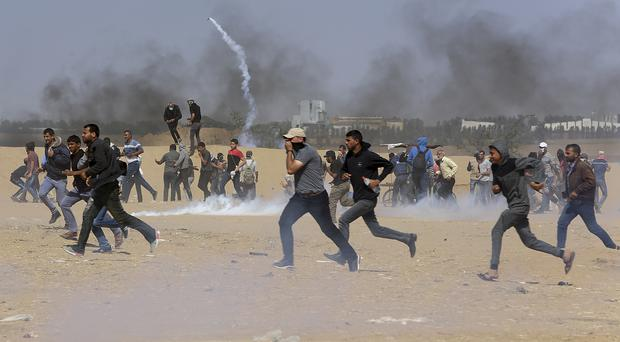 Palestinian protesters run for cover from Israeli troops