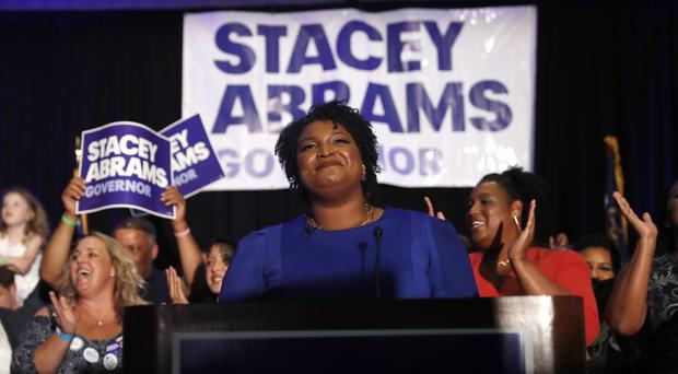 Georgia Democratic gubernatorial candidate Stacey Abrams smiles before speaking to supporters during an election-night watch party in Atlanta (John Bazemore/AP)