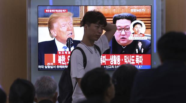 People watch a TV screen showing Donald Trump and Kim Jong Un