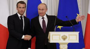 Russian President Vladimir Putin, right, gestures as he shakes hands with French President Emmanuel Macron (Dmitri Lovetsky/AP)
