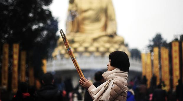 A worshipper offers prayer in front of a Buddha statue at the Huayan Temple (Chinatopix/AP)