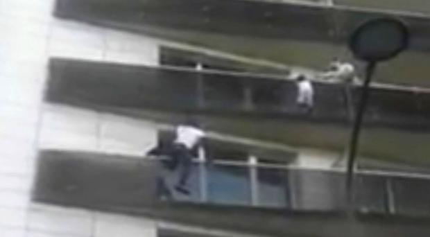 Mamoudou Gassama scales an apartment building to save a young child dangling from a balcony (AP)