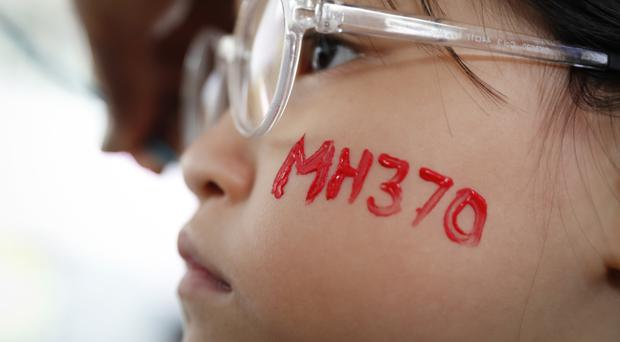 A girl has her face painted during a Day of Remembrance for MH370 in Kuala Lumpur (Vincent Thian/AP)