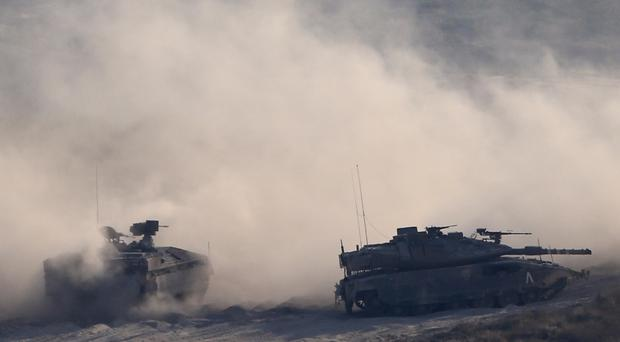 Israeli tanks take up positions along the border with the Gaza strip, (Ariel Schalit/AP)