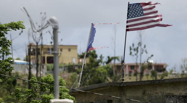 Flags fly on a roof eight months after the passing of Hurricane Maria in the Barrio Jacana Piedra Blanca area of Yabucoa (AP)