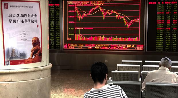 Investors monitor stock prices in a brokerage house in Beijing on Wednesday (AP Photo/Mark Schiefelbein)