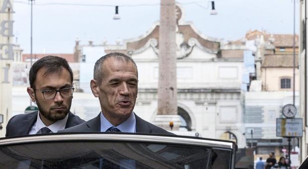 Premier-designate Carlo Cottarelli, centre, gets in a car as he leaves his hotel in Rome (Angelo Carconi/ANSA via AP)