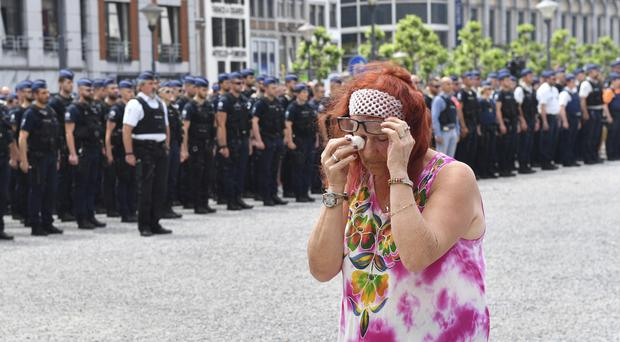 A woman cries as she walks by police officers during a moment of silence for shooting victims near the City Hall in Liege, Belgium (AP)
