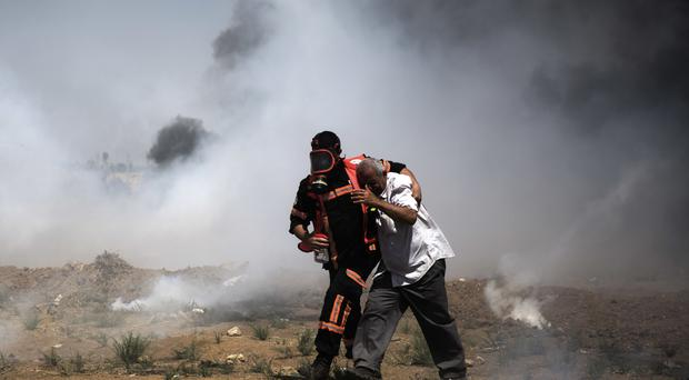 A Palestinian medic helps a man suffering from the effects of teargas fired by Israeli troops (AP)