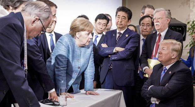 Angela Merkel speaks with Donald Trump during the G7 leaders' summit in Quebec (Jesco Denzel/German Federal Government via AP)