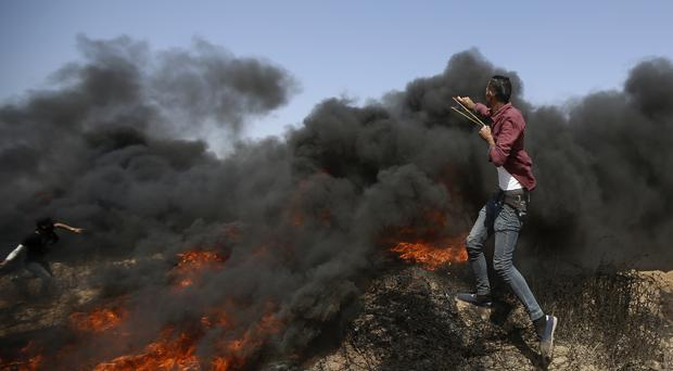 Palestinians hurl stones and burn tyres near the fence of the Gaza Strip's border with Israel (AP)