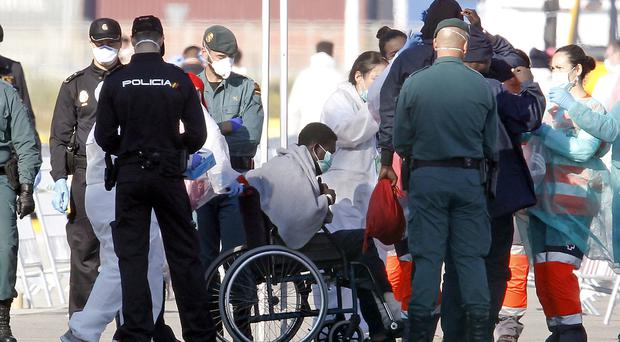 Migrants are checked by emergency workers after arriving in Valencia Alberto Saiz/AP)