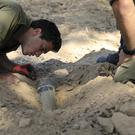 Israeli soldiers inspect a missile launched from Gaza (AP Photo/Tsafrir Abayov)