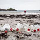 A volunteer collecting plastic on a beach in Isle of Mull, Scotland (Will Rose/Greenpeace/PA)