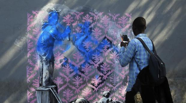 A migrant takes a picture of graffiti believed to be attributed to street artist Banksy (AP)