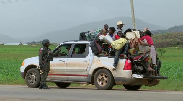 Security personal at a check point observe a pickup truck loaded with people (AP)