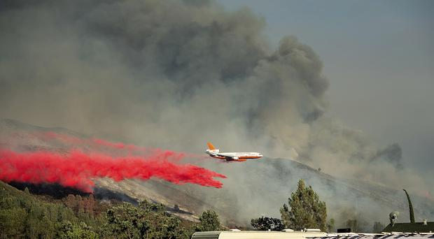 An air tanker drops retardant on a wildfire burning above the Spring Lakes community (AP)
