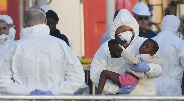 A child is taken from the ship after it docked at the Valletta port (AP)