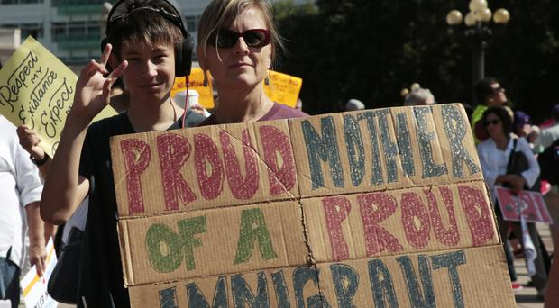 Linda Land-Classon, right, holds up a sign with her 15-year-old son, Ivan, during an immigration rally and protest in Denver (David Zalubowski/AP)